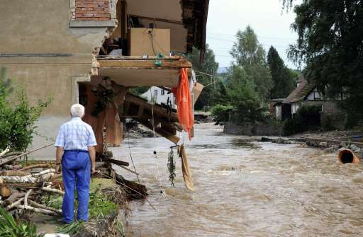 A resident of Bogadynia looks on as his son checks the demaged to their house on August 8, 2010 in Bogadynia, southern Poland. Eight people died and thousands were evacuated amid disrupted traffic and power outages as floods hit parts of central Europe following heavy rainfall on August 7, 2010, rescuers said.PHOTO AFP/ MICHAL CIZEK