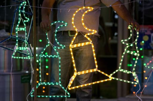 A Palestinian man arranges neon lights and other decorations for the upcoming Muslim holy month of Ramadan at his store in Jerusalem, on August 8, 2010. The start of Ramadan, the ninth and holiest month in the Muslim calendar, is traditionally determined by the sighting of a new moon. AFP PHOTO/AHMAD GHARABLI