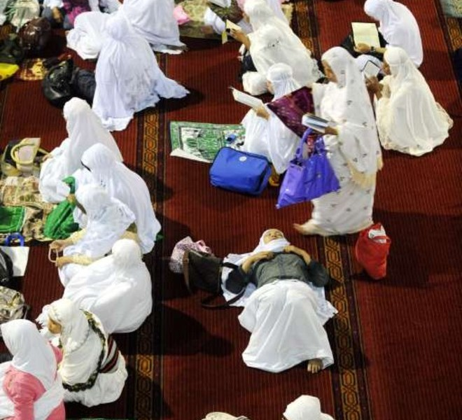 Indonesian Muslim women rest prior to prayers during the first night of Ramadan in Jakarta on August 10, 2010. The fasting month of Ramadan, which starts on August 11, is the ninth month of the Muslim Hijri calendar, during which the faithful abstain from eating, drinking, smoking and having sex during daylight and, in the evening, eat small meals and conduct evening prayers. AFP PHOTO / ADEK BERRY