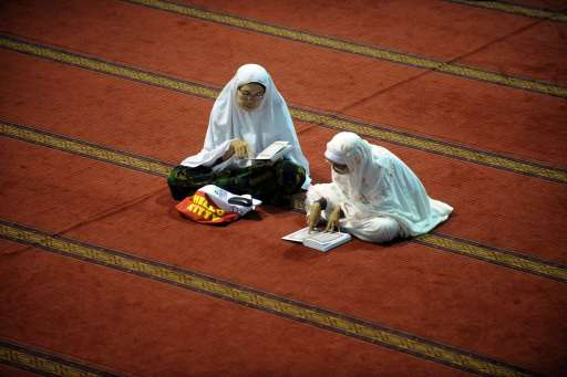 Indonesian women read copies of the Koran during the first night of Ramadan in Jakarta on August 10, 2010. The fasting month of Ramadan, which starts on August 11, is the ninth month of the Muslim Hijri calendar, during which the faithful abstain from eating, drinking, smoking and having sex during daylight and, in the evening, eat small meals and conduct evening prayers. AFP PHOTO / ADEK BERRY