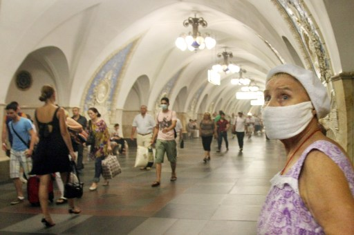 An elderly Russian woman wears a face mask to protect herself from acrid smoke inside the Moscow metro on August 9, 2010.   The toxic smog smothering Moscow showed little sign of abating as media accused officials of covering up the scale of the disaster and the authorities raced to put out a fire near a nuclear site.   AFP PHOTO / ANDREY SMIRNOV