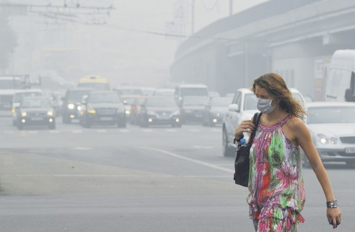 A Russian woman wears a face mask to protect herself from acrid smoke while walking in central Moscow on August 9, 2010.  The daily mortality rate in Moscow has nearly doubled amid a forest fire smog filled record heatwave, with hundreds of extra deaths each day compared to a normal period, the city's top health official said. TOPSHOTS  AFP PHOTO / NATALIA KOLESNIKOVA