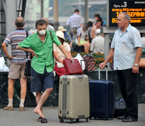 A Russian man wears a face mask to protect himself from forest fire smoke while waiting for a train window in Moscow on August 10, 2010.  A member of the Russian armed forces has been killed fighting wildfires around a major nuclear research centre in the town of Sarov, the defence ministry said.   AFP PHOTO / VIKTOR DRACHEV
