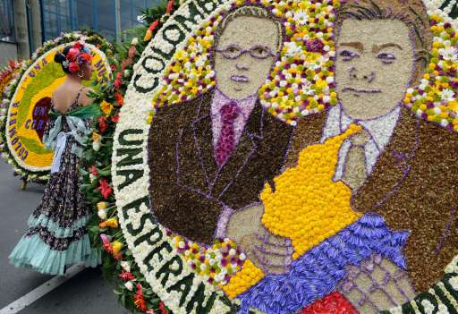 "A woman walks next to a ""silleta"" flower arrangements depicting outgoing Colombian president Alvaro Uribe and new Colombian President Juan Manuel Santos on August 8, 2010, during the traditional ""Silleteros"" Parade of the Flower Fair in Medellin , Antioquia deparment, Colombia.  AFP PHOTO/Raul ARBOLEDA"