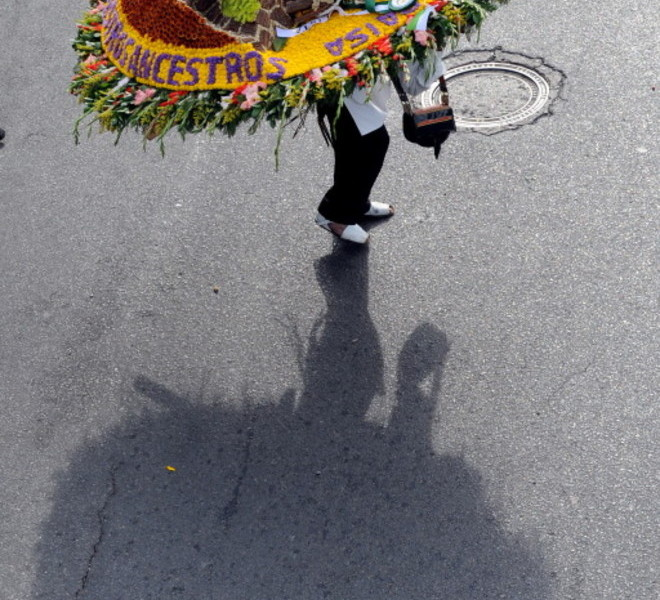 "A farmer walks along the street carrying a ""silleta"" flower arrangement on August 8, 2010, during the traditional ""Silleteros"" Parade of the Flower Fair in Medellin , Antioquia deparment, Colombia. Colombia is one of the major flower exporters in the world. AFP PHOTO/Raul ARBOLEDA"