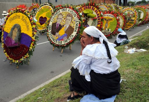 "A farmer sits next to ""silletas"" flower arrangements on August 8, 2010, during the traditional ""Silleteros"" Parade of the Flower Fair in Medellin , Antioquia deparment, Colombia. Colombia is one of the major flower exporters in the world. AFP PHOTO/Raul ARBOLEDA"