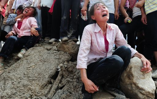 Relatives grieve the loss of a loved one just pulled out from the mud resulting from the devastating landslide in Zhouqu on August 10, 2010 in northwest China's Gansu province. Rescuers in northwest China on August 10 battled on with the grim task of searching for over 1,100 people missing in huge mudslides that have killed 337, but hopes faded that many would be saved. At least three villages were levelled by an avalanche of mud and rocks triggered by heavy rains Saturday in a remote area of Gansu province, the latest deadly disaster as China battles its worst flooding in a decade.  TOPSHOTS  AFP PHOTO / Frederic J. BROWN