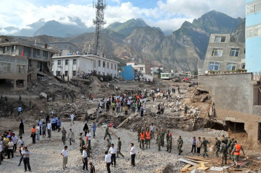 Rescuers and survivors gather as search operations continue after a deadly flood-triggered landslide hit Zhouqu, causing flooding in northwest China's Gansu province on August 8, 2010. Soldiers and rescuers battled on August 9 through an avalanche of sludge and debris as they raced to find survivors of mudslides that killed at least 127 people and left 1,300 missing in northwest China. TOPSHOTS  CHINA OUT    AFP PHOTO