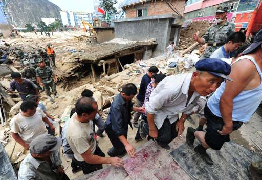Militay personnel evacuate residents amid the rubble of landslide devastation as rescue efforts continue in Zhouqu on August 11, 2010 in northwest China's Gansu province. Hopes of finding survivors of China's worst mudslides in decades is fading  as the death toll topped 700, with more than 1,000 people still missing under an avalanche of rock and sludge. More than 10,000 soldiers and rescuers combed through the mountains of mud that buried a remote area of the northwest province of Gansu at the weekend, but 72 hours after the disaster, the window of survival was quickly closing. AFP PHOTO/Frederic J. BROWN