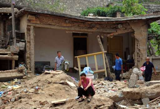 A surviving resident reacts to her surroundings amid the rubble of landslide devastation in Zhouqu on August 11, 2010 in northwest China's Gansu province. Hopes of finding survivors of China's worst mudslides in decades is fading as the death toll topped 700, with more than 1,000 people still missing under an avalanche of rock and sludge. More than 10,000 soldiers and rescuers combed through the mountains of mud that buried a remote area of the northwest province of Gansu at the weekend, but 72 hours after the disaster, the window of survival was quickly closing.   AFP PHOTO / Frederic J. BROWN