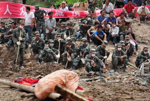 Military personnel sit while awaiting further instructions for rescue and cleanup operations behind a dead body covered in blankets amid the rubble of landslide devastation in Zhouqu on August 11, 2010 in northwest China's Gansu province. Hopes of finding survivors of China's worst mudslides in decades is fading  as the death toll topped 700,with more than 1,000 people still missing under an avalanche of rock and sludge. More than 10,000 soldiers and rescuers combed through the mountains of mud that buried a remote area of the northwest province of Gansu at the weekend, but 72 hours after the disaster, the window of survival was quickly closing.  AFP PHOTO / Frederic J. BROWN