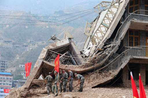 Military personnel on clean-up operations work beside a demolished building amid the rubble of landslide devastation in Zhouqu on August 11, 2010 in northwest China's Gansu province. Hopes of finding survivors of China's worst mudslides in decades is fading as the death toll topped 700, with more than 1,000 people still missing under an avalanche of rock and sludge. More than 10,000 soldiers and rescuers combed through the mountains of mud that buried a remote area of the northwest province of Gansu at the weekend, but 72 hours after the disaster, the window of survival was quickly closing. AFP PHOTO/Frederic J. BROWN