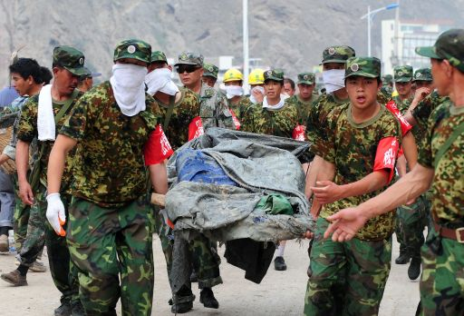 Military personnel carry a dead body recovered amid the rubble of landslide devastation to an outdoor temporary morgue as rescue and cleanup operations continue in Zhouqu on August 11, 2010 in northwest China's Gansu province. Hopes of finding survivors of China's worst mudslides in decades is fading as the death toll topped 700, with more than 1,000 people still missing under an avalanche of rock and sludge. More than 10,000 soldiers and rescuers combed through the mountains of mud that buried a remote area of the northwest province of Gansu at the weekend, but 72 hours after the disaster, the window of survival was quickly closing.   AFP PHOTO / Frederic J. BROWN