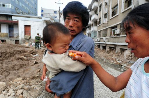 A woman offers a child something to eat amid the rubble of landslide devastation as rescue and clean-up operations continue in Zhouqu on August 11, 2010 in northwest China's Gansu province. Hopes of finding survivors of China's worst mudslides in decades is fading as the death toll topped 700, with more than 1,000 people still missing under an avalanche of rock and sludge. More than 10,000 soldiers and rescuers combed through the mountains of mud that buried a remote area of the northwest province of Gansu at the weekend, but 72 hours after the disaster, the window of survival was quickly closing.   AFP PHOTO / Frederic J. BROWN