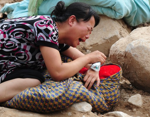 A woman cries over the dead body of her child wapped in blankets amid the rubble of landslide devastation in Zhouqu on August 11, 2010 in northwest China's Gansu province. Hopes of finding survivors of China's worst mudslides in decades is fading  as the death toll topped 700, with more than 1,000 people still missing under an avalanche of rock and sludge. More than 10,000 soldiers and rescuers combed through the mountains of mud that buried a remote area of the northwest province of Gansu at the weekend, but 72 hours after the disaster, the window of survival was quickly closing. TOPSHOTS AFP PHOTO/Frederic J. BROWN