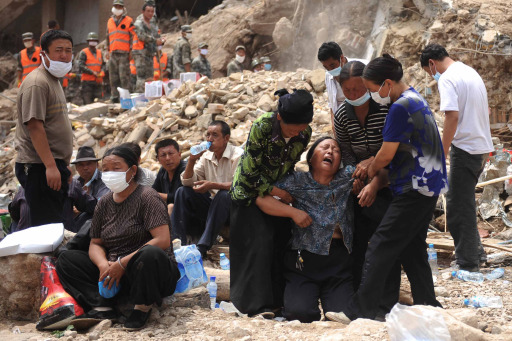 A Chinese woman cries among the rubble as rescuers and survivors rest after the massive landslide in Zhouqu, northwest China's Gansu province on August 11, 2010. Fresh heavy rains brought more misery to a town in northwest China devastated by mudslides that have already killed more than 1,100, with new floods leaving more people missing.   CHINA OUT    AFP PHOTO