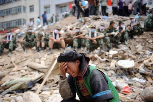 A Chinese woman cries among the rubble as rescuers take a break after the massive landslide in Zhouqu, northwest China's Gansu province on August 11, 2010. Fresh heavy rains brought more misery to a town in northwest China devastated by mudslides that have already killed more than 1,100, with new floods leaving more people missing.  TOPSHOTS  CHINA OUT    AFP PHOTO