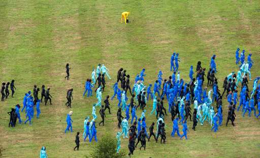 Members of the public leave the area after taking part in a naked installation for American artist Spencer Tunick at the Big Chill festival near Ledbury in Herefordshire on August 8, 2010. Those involved were painted in body paints and shot from above to create patterns and designs for Tunick's photographs. Running from the 5th to the 8th of August, the festival features some of the more popular bands and musicians from the underground music scene as well more established acts such as Lily Allen and Massive Attack. AFP PHOTO/Leon Neal