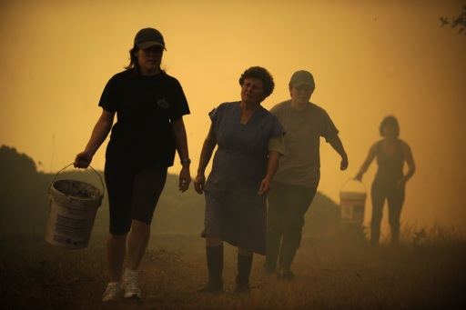 Porqueira?s residents walk with buckets near fires in Porqueira, August 14, 2010, near A Coru?a.       TOPSHOTS/AFP PHOTO/Pedro ARMESTRE