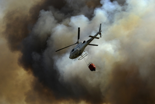 An helicopter drops water to extinguish a fire in Cualedro, near Ourense, on August 10, 2010.         TOPSHOTS/AFP PHOTO/Pedro ARMESTRE