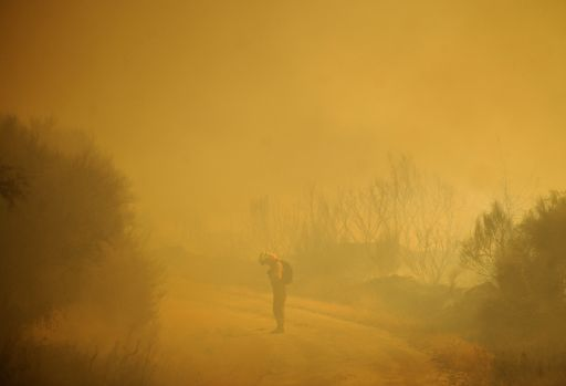 A member of the fire brigade works around the area where a fire burns in Cualedro, near Ourense, on August 10, 2010.        TOPSHOTS/AFP PHOTO/Pedro ARMESTRE