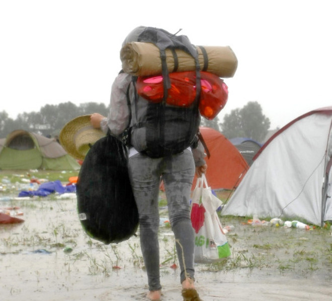 A camper walks on August 16, 2010 in a flooded camping site at the festival Feest in het Park, after heavy rainfall, in Oudenaarde. Some 2000 people were evacuated from the site as the camping field was completely flooded following serious rainfall overnight.   AFP PHOTO/ BELGA PHOTO / PETER DECONINCK