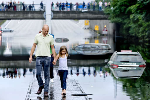 TOPSHOTS A father and his daughter are walking on the center of a highway exit in Copenhagen on August 15, 2010 where several cars still are trapped in the water masses after the heavy rain in the area og Copenhagen and North Sealand last night.  AFP PHOTO/ Bax Lindhardt/Scanpix