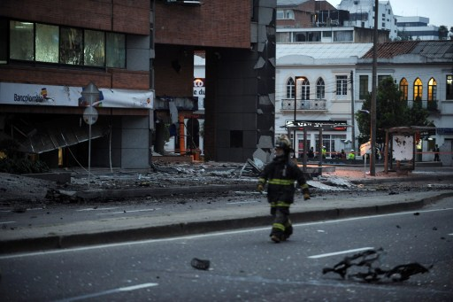 Firefighter inspects the site of an explosion in Bogota, Colombia on early August 12, 2010. A powerful explosion rocked northern Bogota early Thursday, causing extensive damage to a private radio station and shattering windows of buildings in the area, witnesses said. Police were investigating the possibility the explosion was caused by a car bomb, Bogota police commander Cesar Pinzon told Radio Caracol, which was hit by the blast. There were no immediate reports of casualties. AFP PHOTO/Eitan Abramovich