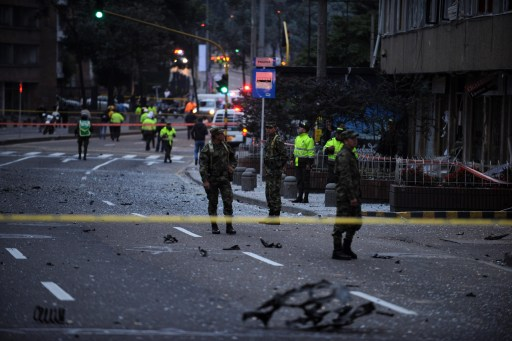 Colombian soldiers and police officers inspect the site of an explosion in Bogota, Colombia on early August 12, 2010. A powerful explosion rocked northern Bogota early Thursday, causing extensive damage to a private radio station and shattering windows of buildings in the area, witnesses said. Police were investigating the possibility the explosion was caused by a car bomb, Bogota police commander Cesar Pinzon told Radio Caracol, which was hit by the blast. There were no immediate reports of casualties. AFP PHOTO/Eitan Abramovich