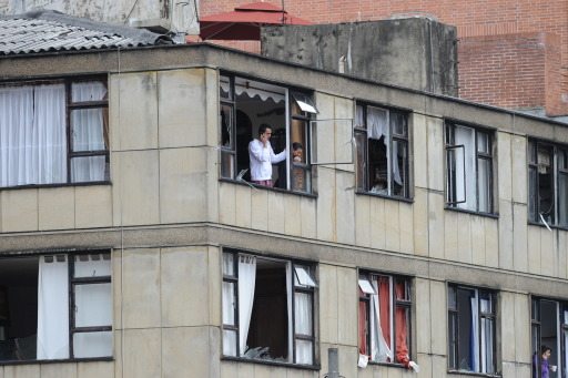 People look out through broken windows of a damaged building after an explosion in Bogota, Colombia, on early August 12, 2010. A powerful explosion rocked northern Bogota early Thursday, causing extensive damage to a private radio station and shattering windows of buildings in the area, witnesses said. Police were investigating the possibility the explosion was caused by a car bomb, Bogota police commander Cesar Pinzon told Radio Caracol, which was hit by the blast. There were no immediate reports of casualties. AFP PHOTO/Rodrigo ARANGUA