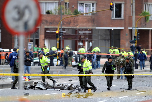 Colombian police officers inspect the site of an explosion in Bogota, Colombia, on early August 12, 2010. A powerful explosion rocked northern Bogota early Thursday, causing extensive damage to a private radio station and shattering windows of buildings in the area, witnesses said. Police were investigating the possibility the explosion was caused by a car bomb, Bogota police commander Cesar Pinzon told Radio Caracol, which was hit by the blast. There were no immediate reports of casualties. AFP PHOTO/Rodrigo ARANGUA