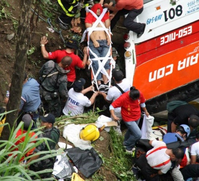 Rescuers try to remove bodies of bus passengers from the wreckage after it plunged into a deep ravine in the village Bangaan, part of the own of Sablan, in Benguet province in the northern Philippines on August 18, 2010. Thirty-five people were killed when the packed passenger bus plunged into a deep ravine in the northern Philippines on August 18, authorities said said. The bus, carrying 47 Filipinos, had just left the mountain resort city of Baguio when its brakes failed, local fire chief Senior Superintendent Richard Villanueva told AFP.      AFP PHOTO