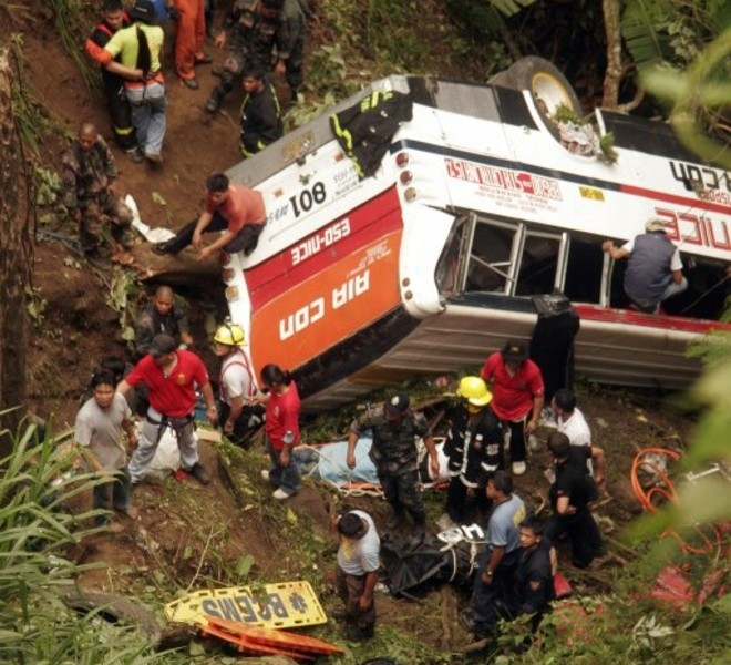 Rescuers try to remove bodies of bus passengers from the wreckage after it plunged into a deep ravine in the village Bangaan, Sablan town, province of Benguet in northern Philippines on August 18, 2010 killing 35 people. The bus, carrying 47 Filipinos, had just left the mountain resort city of Baguio when its brakes failed, local fire chief Senior Superintendent Richard Villanueva told AFP.  AFP PHOTO/JJ LANDINGIN