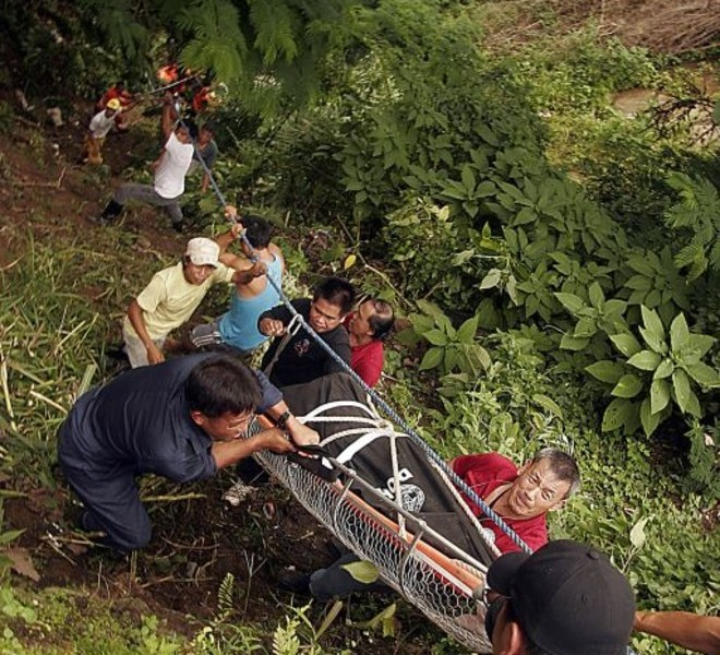 Rescuers and residents use an improvished carrier to remove bodies of bus passengers from the wreckage after it plunged into a deep ravine in the village Bangaan, Sablan town, province of Benguet in northern Philippines on August 18, 2010 killing 35 people. The bus, carrying 47 Filipinos, had just left the mountain resort city of Baguio when its brakes failed, local fire chief Senior Superintendent Richard Villanueva told AFP.  AFP PHOTO/JJ LANDINGIN