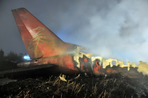 The tail-end wreckage of the Henan Airlines ERJ-190 jet made by Brazilian company Embraer which was carrying 96 people sits smoldering after it slammed into the ground on landing in the northeast city of Yichun in remote Heilongjiang province on August 25, 2010.  The Chinese airliner smashed into two pieces while trying to land in heavy fog, leaving at least 42 people dead but 54 survivors in the country's first major air disaster in nearly six years.          CHINA OUT    AFP PHOTO