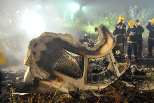 Chinese firefighters search the cockpit of the Henan Airlines ERJ-190 jet wreckage at the crashsite in the northeast city of Yichun in remote Heilongjiang province early on August 25, 2010.  A Chinese airliner smashed into two pieces while trying to land in heavy fog, leaving at least 42 people dead but 54 survivors in the country's first major air disaster in nearly six years.          CHINA OUT    AFP PHOTO