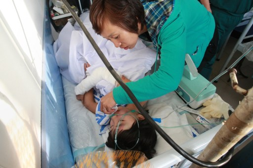 A family member attends to a crash survivor injured when a Henan Airlines plane carrying 96 people slammed into the ground on landing in the northeast city of Yichun in remote Heilongjiang province on August 25, 2010. The Chinese airliner smashed into two pieces while trying to land in heavy fog, leaving at least 42 people dead but 54 survivors in the country's first major air disaster in nearly six years.          CHINA OUT    AFP PHOTO