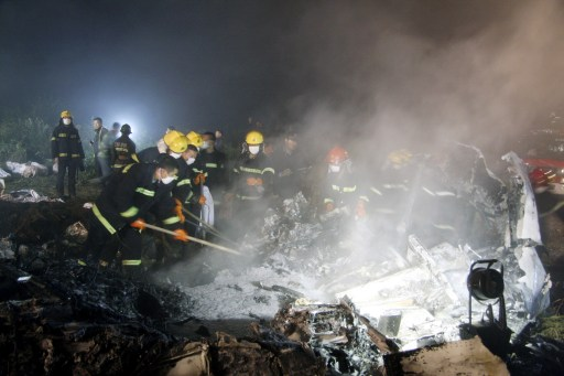 Chinese firefighters search for victims in the wreckage of the Henan Airlines ERJ-190 jet made by Brazilian company Embraer which was carrying 96 people when it slammed into the ground on landing in the northeast city of Yichun in remote Heilongjiang province on August 25, 2010.  The Chinese airliner smashed into two pieces while trying to land in heavy fog, leaving at least 42 people dead but 54 survivors in the country's first major air disaster in nearly six years.          CHINA OUT    AFP PHOTO