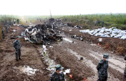 Bodies (R) of the victims recovered from the wreckage of the Henan Airlines ERJ-190 jet made by Brazilian company Embraer lie beside the wreckage in the northeast city of Yichun in remote Heilongjiang province on August 25, 2010. The Chinese airliner smashed into two pieces while trying to land in heavy fog, leaving at least 42 people dead but 54 survivors in the country's first major air disaster in nearly six years.          CHINA OUT    AFP PHOTO