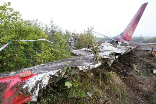 Chinese soldiers (C) watch over the wreckage of the Henan Airlines ERJ-190 jet made by Brazilian company Embraer in the northeast city of Yichun in remote Heilongjiang province on August 25, 2010.  The Chinese airliner smashed into two pieces while trying to land in heavy fog, leaving at least 42 people dead but 54 survivors in the country's first major air disaster in nearly six years.          CHINA OUT    AFP PHOTO