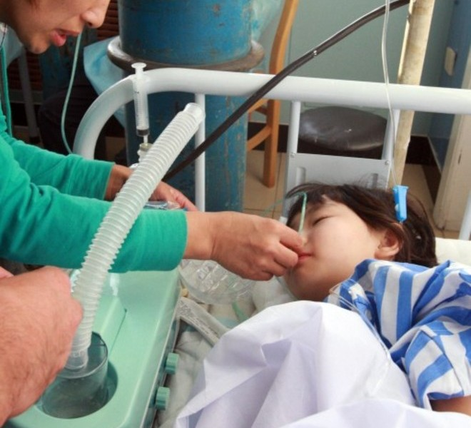 A young Chinese child who survived the Henan Airlines ERJ-190 jet crash is cared by family members at a hospital in the northeast city of Yichun in remote Heilongjiang province on August 25, 2010.  A Chinese airliner smashed into two pieces while trying to land in heavy fog, leaving at least 42 people dead but 54 survivors in the country's first major air disaster in nearly six years.          CHINA OUT    AFP PHOTO