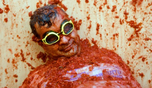 "A man is pelted with tomatoes during the ""Tomatina"" Festival on August 25, 2010  in Bunol, Valencia region in southeastern Spain.  Tens of thousands of revellers from around the world pelted each other with tonnes of tomatoes Wednesday in a mushy festival in the eastern Spanish town of Bunol. The town council brought in some 100 tonnes of ripe tomatoes on trucks for the estimated 40,000 tourists who descended on the town of just 9,000 inhabitants for the annual festival, which has taken place for more than 60 years. AFP PHOTO / Biel Ali?o"