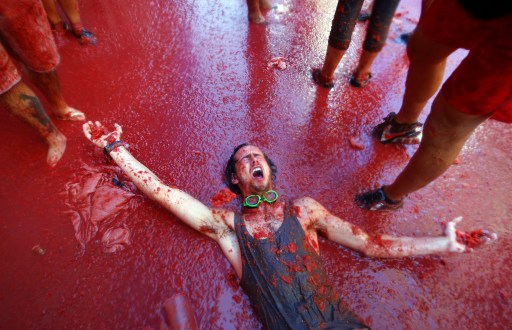 "A man is pelted with tomatoes during the ""Tomatina"" Festival on August 25, 2010  in Bunol, Valencia region in southeastern Spain.  Tens of thousands of revellers from around the world pelted each other with tonnes of tomatoes Wednesday in a mushy festival in the eastern Spanish town of Bunol. The town council brought in some 100 tonnes of ripe tomatoes on trucks for the estimated 40,000 tourists who descended on the town of just 9,000 inhabitants for the annual festival, which has taken place for more than 60 years. AFP PHOTO / Biel Alino"