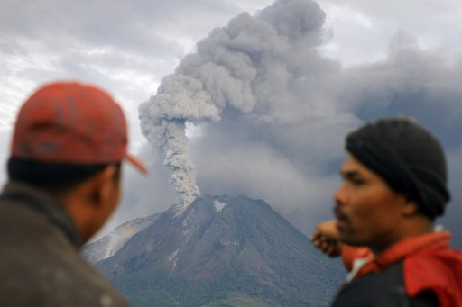 Residents observe the eruption of Mount Sinabung on August 30, 2010 from their village in Tanah Karo in North Sumatra.  Airlines on August 30 were warned to avoid remote Mount Sinabung in northern Sumatra as the volcano spewed a vast cloud of smoke and ash high into the air for a second day after springing to life for the first time in four centuries on August 29.  AFP PHOTO / SUTANTA ADITYA