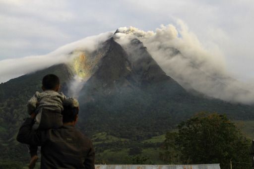 A man and his son look as the Sinabung volcano spews thick smoke in Karo district in North Sumatra on August 29, 2010. Indonesia issued a red alert after the  Sinabung volcano on the island of Sumatra erupted, spewing smoke and ash 1,500 metres into the air and sending thousands of people fleeing from their homes. AFP PHOTO / SUTANTA ADITYA