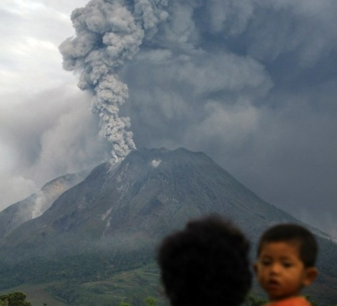 An Indonesian woman carrying a child observes the eruption of Mount Sinabung on August 30, 2010 from her village in Tanah Karo in North Sumatra. Airlines on August 30 were warned to avoid remote Mount Sinabung in northern Sumatra as the volcano spewed a vast cloud of smoke and ash high into the air for a second day after springing to life for the first time in four centuries on August 29.  AFP PHOTO / SUTANTA ADITYA