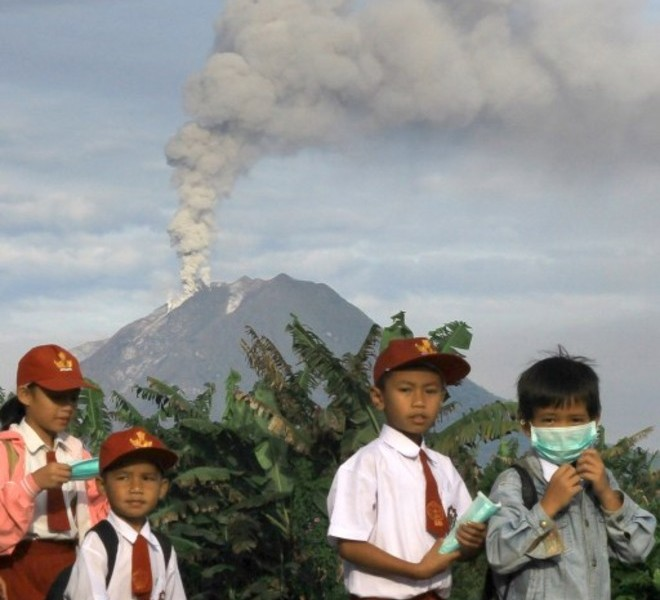 Indonesian school children walk home after schools were suspended in Tanah Karoh due to the eruption of Mount Sinabung (background) in North Sumatra on August 30, 2010. Airlines on August 30 were warned to avoid remote Mount Sinabung in northern Sumatra as the volcano spewed a vast cloud of smoke and ash high into the air for a second day after springing to life for the first time in four centuries on August 29.  AFP PHOTO / SUTANTA ADITYA
