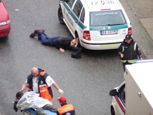 A handout photo provided by the Slovak SME daily newspaper shows paramedics (L) attending to an injured Slovak police officer on August 30, 2010 in the Bratislava suburb of Devinska Nova Ves, where a man armed with a shotgun opened fire in a street, killing six people and injuring 14, according to emergency services. The police refused to comment, saying they were still investigating the shooting.      AFP PHOTO/SME