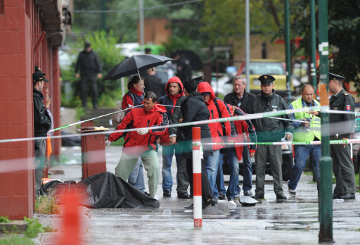 Police and rescuers stand near a slain man on August 30, 2010 in the Bratislava suburb of Devinska Nova Ves, where a man armed with a shotgun opened fire in a street, killing six people and injuring 19, according to emergency services. The SME daily said on its website that the shooter was a 15-year-old drug addict, who shot himself dead after the rampage in Devinska Nova Ves. AFP PHOTO / SAMUEL KUBANI