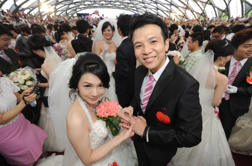 A couple poses for photos during a mass wedding ceremony organized by Taipei city covernment on September 9, 2010. More than 160 new couples and hundreds of their relatives take part in this group wedding ceremony.      AFP PHOTO / Sam YEH